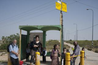 Hitchhikers standing by a road in the West Bank