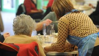 A woman serves food while an older woman sits at the table