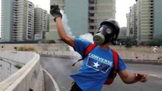 A protester in Venezuala throws back a tear gas canister