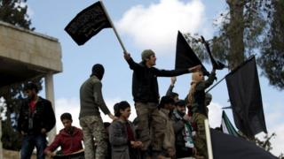 Protesters carry Nusra Front flags and shout slogans during an anti-government protest after Friday prayers in the town of Marat Numan, Idlib province 11/03/2016