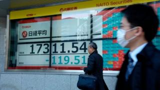 Pedestrians pass a stock markets board in Tokyo (16 March 2020)