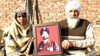सुखजिंदर सिंह की तस्वीर लिए उनके माता-पिता