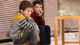 طفلان سوريان يجلسان على رصيف في دوما. 19 أبريل/نيسان 2018