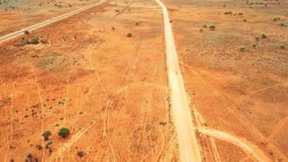 A deserted dirt road in the Australian outback, seen from above
