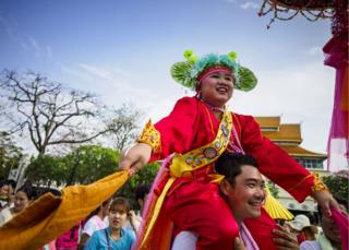A Shan boy is carried around the Three Kings Monument in Chiang Mai during an afternoon procession of Poy Sang Long participants.