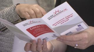 a finger points at a leaflet