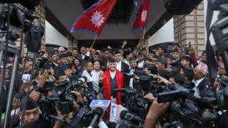 Nepal's newly-appointed prime minister Khadga Prasad Oli (centre) is surrounded by journalists at the Constituent Assembly in Kathmandu (11 October 2015)