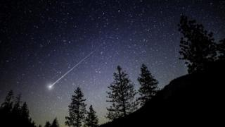 Image shows an asteroid flying across a night sky