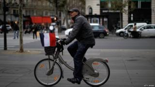 A cyclist carrying a French flag