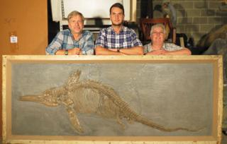 Palaeontologists with one of the fossils