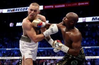 Floyd Mayweather Jr. throws a punch at Conor McGregor during their super welterweight boxing match on 26 August 2017 at T-Mobile Arena in Las Vegas, Nevada.