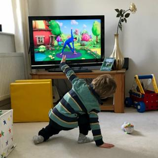 Boy exercising with television