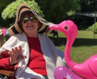Iola Roberts with a pink inflatable flamingo at the