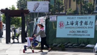 A woman pushes a stroller in San Gabriel, California on May 17, 2016 past a banner at a construction site project financed by the Shanghai Commercial Bank