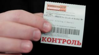 "A man holds a ticket of the ""Death of Stalin"" movie, which was banned from being shown in cinemas of the country on January 24, as he attends its screening at the Pioner Cinema in Moscow, Russia"