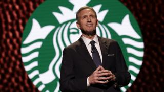 Schultz in front of Starbucks logo onstage in 2017