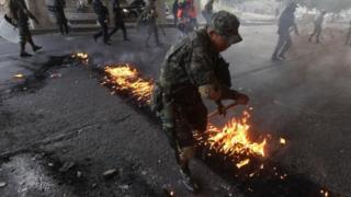 A soldier removes a burning tire set to block a road by opposition supporters during a protest over a disputed presidential election in Tegucigalpa, Honduras, December 11, 2017