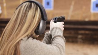 A woman firing a gun