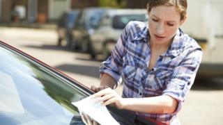 Woman looks at parking notice