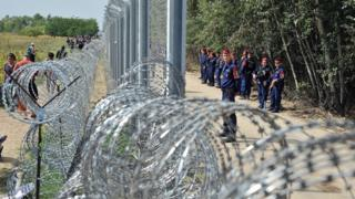 Migrants and refugees walk near razor-wire along a 3-meter-high fence secured by Hungarian police (R) at the official border crossing between Serbia and Hungary, near the northern Serbian town of Horgos on September 15, 2015.
