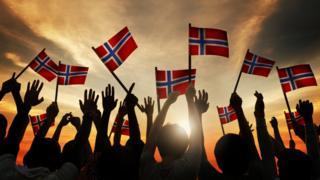 Personas alzan banderas de Noruega