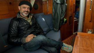 अर्जेंटीना के नाविक जुआन मैनुअल बैलेस्टरो अपने सेलबोट के केबिन में एक तस्वीर के लिए पोज़ देते हैं
