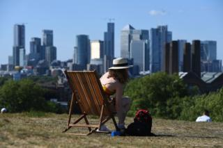 A woman sunbathes on a deck chair in Greenwich Park, with buildings in the distanc