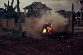 A man lights a fire in Kumasi, Ghana