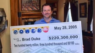 Brad Duke con una réplica del cheque que cobró