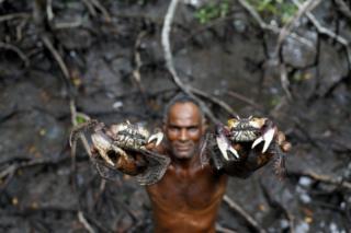 Fisherman Jose da Cruz showing crabs he has caught