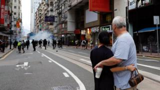 "A couple hugs each other as police fire tear gas into the crowds to disperse anti-national security law protesters during a march at the anniversary of Hong Kong""s handover to China from Britain in Hong Kong, China"