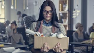Mujer deja su trabajo con una caja en la mano.
