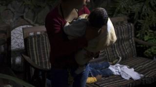 Mujer obligada por las pandillas a cuidar de sus hijos. Foto: Oliver de Ros