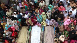 Muslim women and men gathered around three bodies in 2014