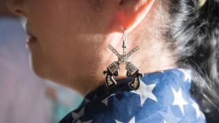 woman with gun earrings
