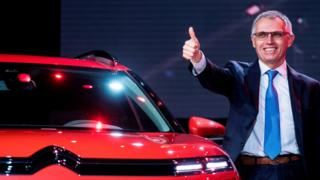 Carlos Tavares, CEO of PSA Peugeot Citroen, gives a thumbs up next to a CitroenC5 Aircross concept car during an event ahead of the 17th Shanghai International Automobile Industry Exhibition in Shanghai on April 18, 2017.