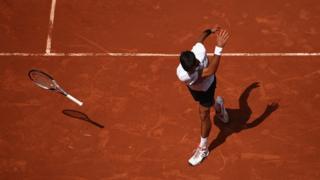 Novak Doković tira la raqueta en el suelo durante un partido