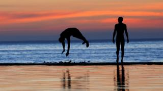 Youths dive into a tidal pool as temperatures soar at Camps Bay beach in Cape Town, South Africa, December 11, 2016.