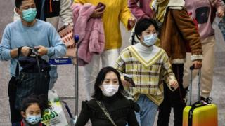 Passengers wearing respiratory masks walk across a terminal on January 31, 2020 in Rome