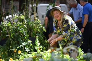 A volunteer admires one of the Parish's moveable pop-up allotments