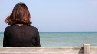 Mulher sozinha em banco na praia