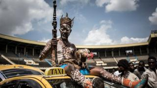 A Congolese wrestler's fetisheur sits on top of a car as he arrives to the Stade De Martyrs for a sports exhibition day in Kinshasa, DR Congo - Tuesday 8 January 2019
