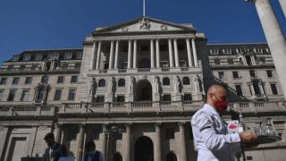 A waiter serves drinks outside of the Bank of England
