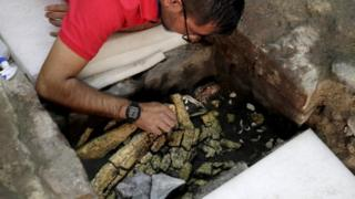 An archaeologist works on a 500-year-old partially-excavated stone box containing an Aztec offering in Mexico City, 25 March 2019