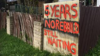 A sign outside a damaged house in Christchurch that reads '5 years, no rebuild, still waiting'