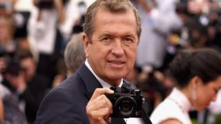 mario testino holds a camera on a red carpet