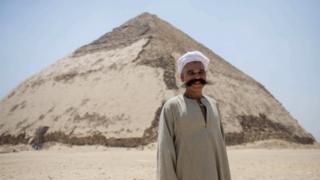 한 남성이 굴절 피라미드 앞에 서 있다