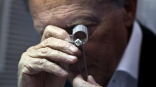 "A trader inspects a diamond at the trading floor of Israel""s Diamond Exchange (IDE) in Ramat Gan near Tel Aviv, Israel March 19, 2013."
