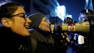 """Protesters outside state TV denounced the new Overtime law as a """"slave law"""" on Monday night"""