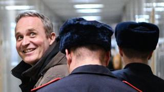 Dennis Christensen is led down a corridor by uniformed police, but looks over his shoulder to smile cheerfully at photographers